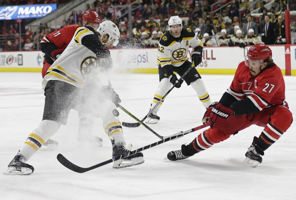 Boston Bruins' Rick Nash and Carolina Hurricanes' Justin Faulk (27) chase the puck during the first period of an NHL hockey game in Raleigh, N.C., Tue