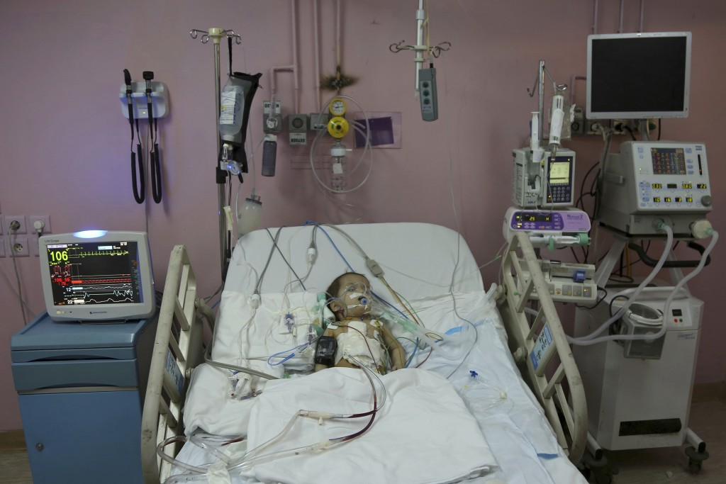 In this March 5, 2018 photo, Syrian refugee Eman Zatima, recovers after her surgery, at a hospital in Amman, Jordan. Eman, who has a heart defect, rec