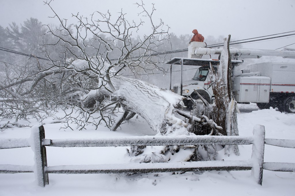 Workers remove a fallen tree from a road and repair power lines during a winter storm, Tuesday, March 13, 2018 in Norwell, Mass. The nor'easter is exp