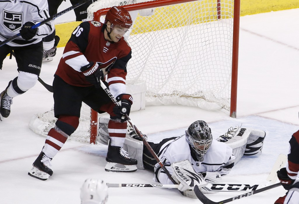 Los Angeles Kings goaltender Jack Campbell, right, gets to the puck before Arizona Coyotes left wing Max Domi (16) during the second period of an NHL