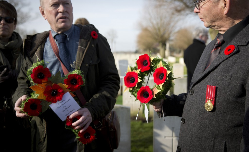 Gary Edmundson, left, from Fort Saskatchewan, Canada, carries flowers for his relative British Private Thomas Edmundson during a re-burial service at