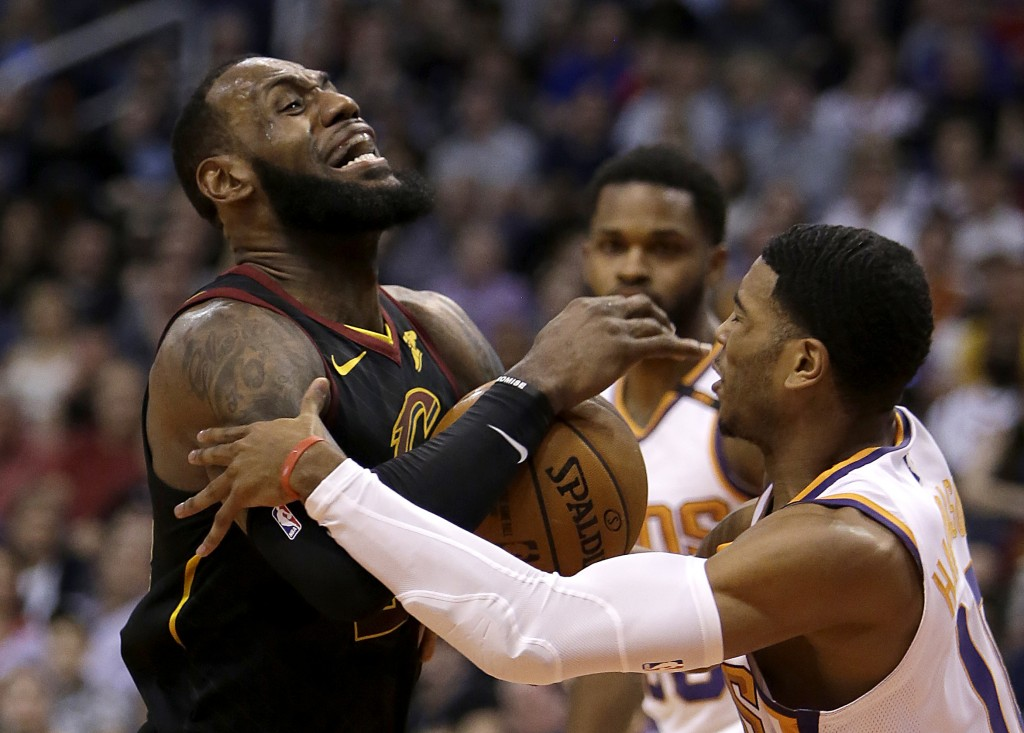 Cleveland Cavaliers forward LeBron James (23) gets fouled by Phoenix Suns guard Shaquille Harrison in the first half during an NBA basketball game, Tu