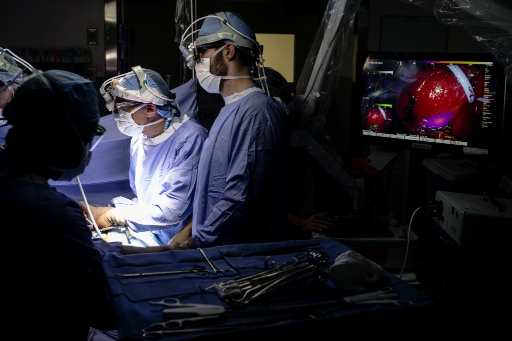 Dr. Sunil Singhal, second from right, directs a special camera to view a tumor in his patient made visible with a fluorescent dye, seen at monitor on