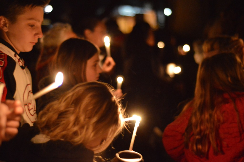 FILE - In this Dec. 7, 2017, file photo, Aztec High School students and area residents gather for a candlelight vigil in Aztec, N.M., after a shooting