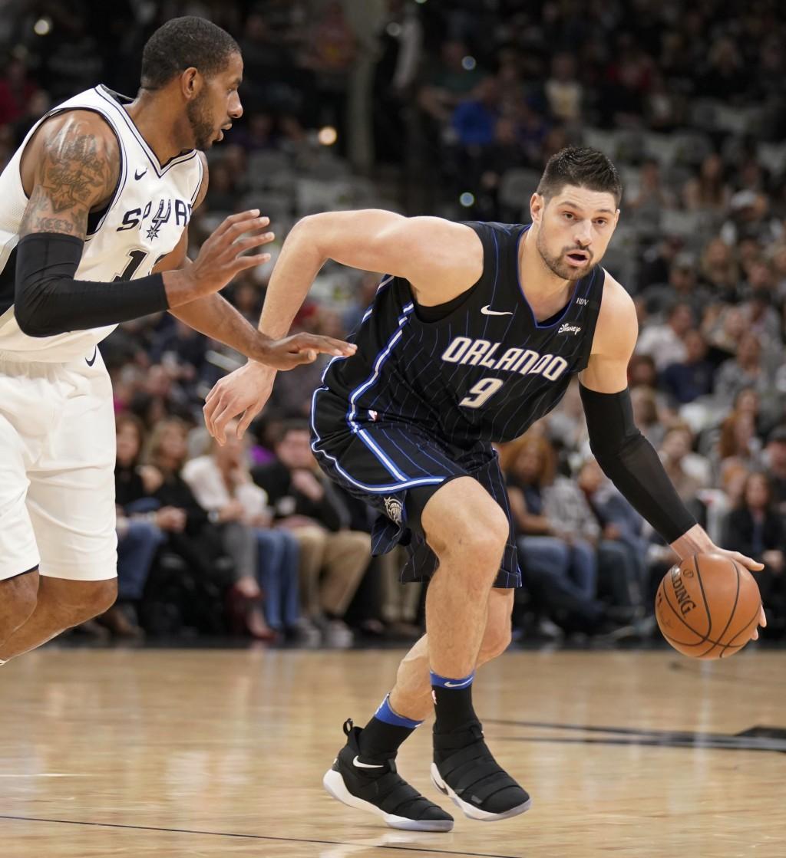 Orlando Magic's Nikola Vucevic (9) drives against San Antonio Spurs' LaMarcus Aldridge during the first half of an NBA basketball game, Tuesday, March