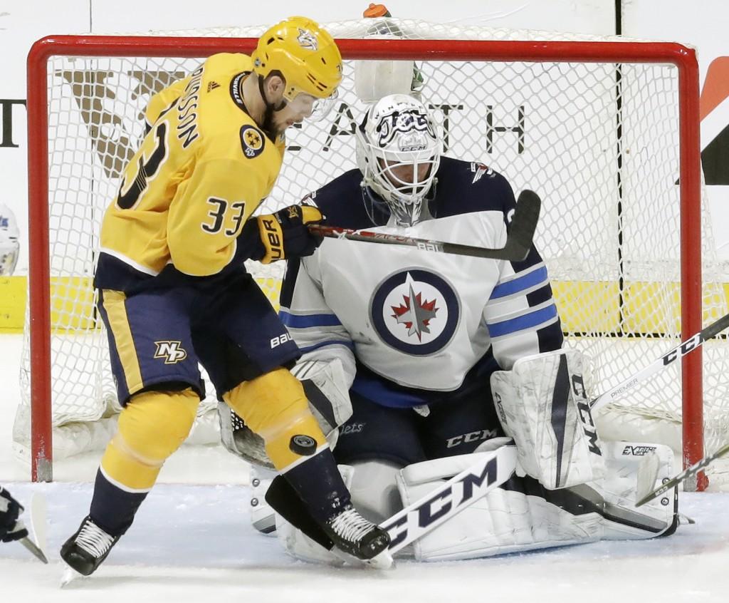 Nashville Predators left wing Viktor Arvidsson (33), of Sweden, tries to deflect the puck against Winnipeg Jets goalie Michael Hutchinson in the first