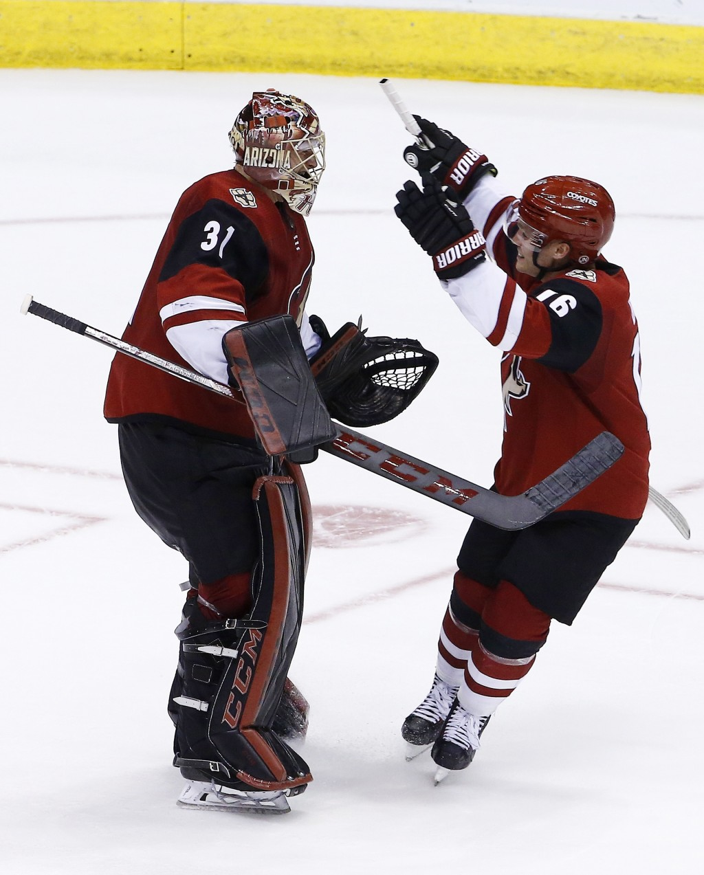 Arizona Coyotes goaltender Adin Hill (31) celebrates his first NHL win with left wing Max Domi (16) after a shootout of an NHL hockey game against the