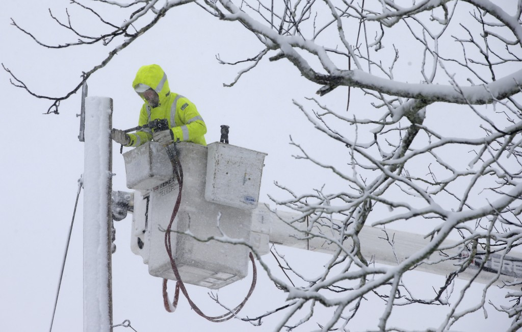 A Worker repairs power lines during a winter storm, Tuesday, March 13, 2018, in Norwell, Mass.  A nor'easter that could deliver up to 2 feet of snow t
