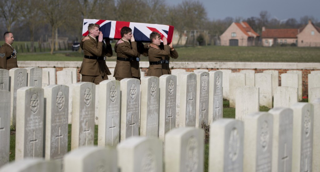 Soldiers carry the flag draped casket of British Private Thomas Edmundson during a re-burial service at CWGC Perth Cemetery in Ypres, Belgium, Wednesd