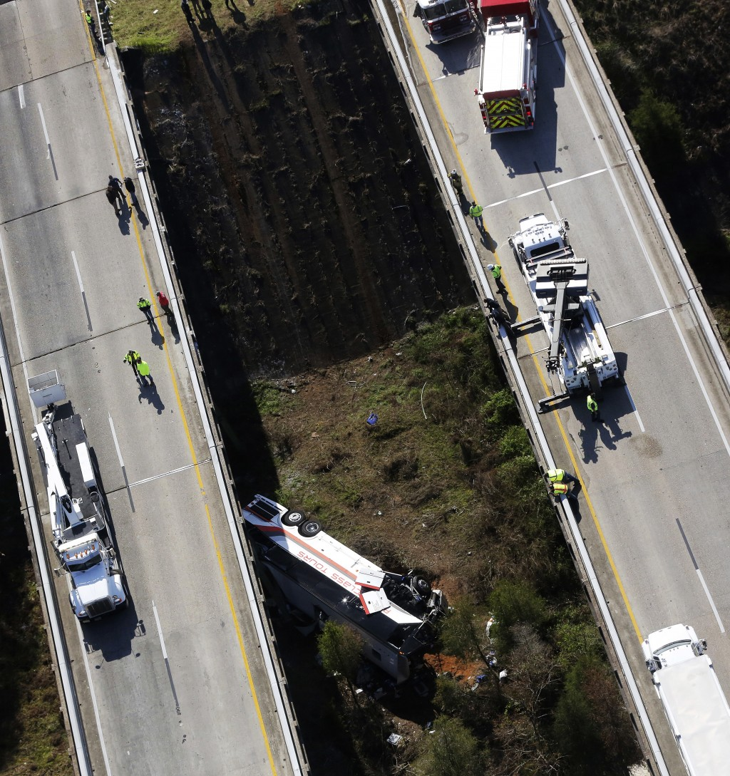 Rescue crews look down on a charter bus after a deadly crash on Tuesday, March 13, 2018, in Loxley, Ala. The bus carrying Texas high school band membe