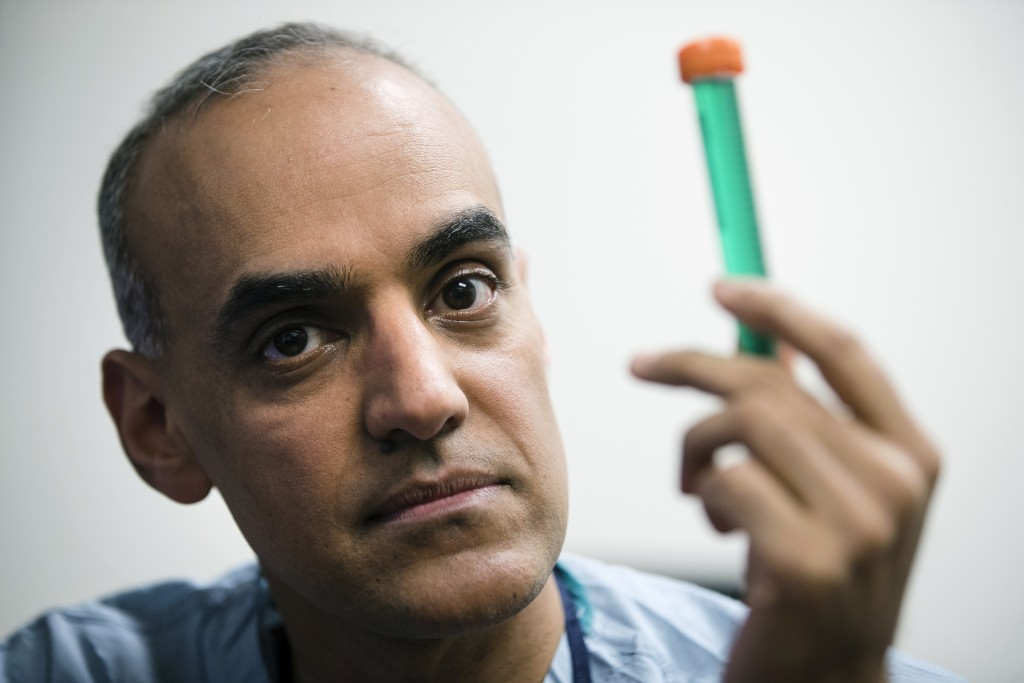 Surgeon Dr. Sunil Singhal poses for a photograph with a vial of fluorescent dye at the Hospital of the University of Pennsylvania in Philadelphia, Tue