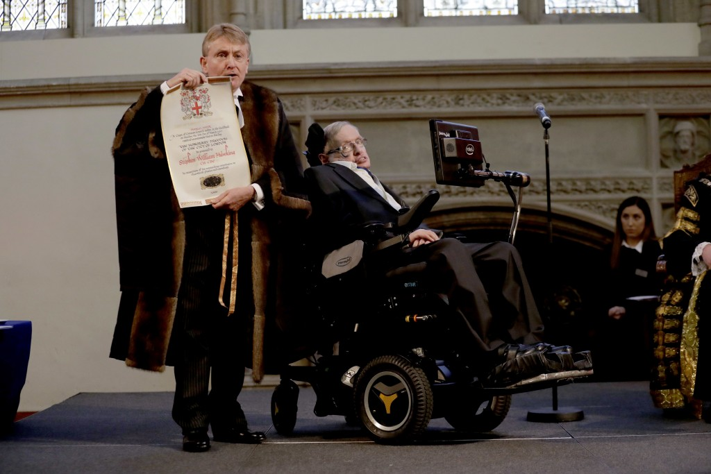 FILE - In this March 6, 2017 file photo, Britain's Professor Stephen Hawking is presented with his illuminated Freedom scroll by the Chamberlain of th