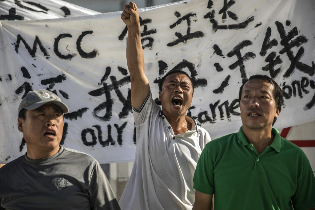 In this July 26, 2017, photo, Chinese laborers Jingbao Zhao, left, Xiaoli Wang, center, and Yongbo Sun, protest in front of the Imperial Pacific Casin