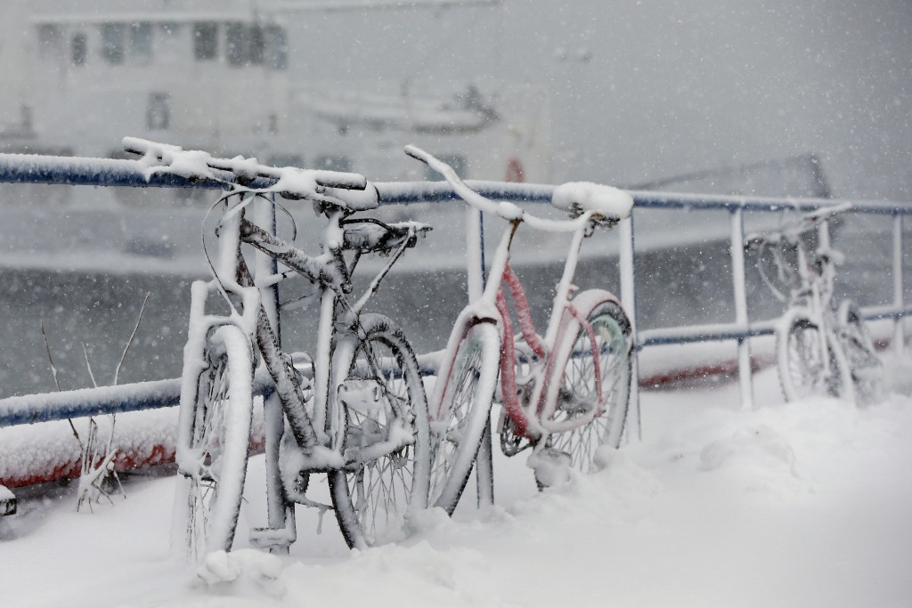 Bicycles are chained to a railing are covered with snow at the Boston Harbor Shipyard and Marina in Boston, Tuesday, March 13, 2018.  The National Wea