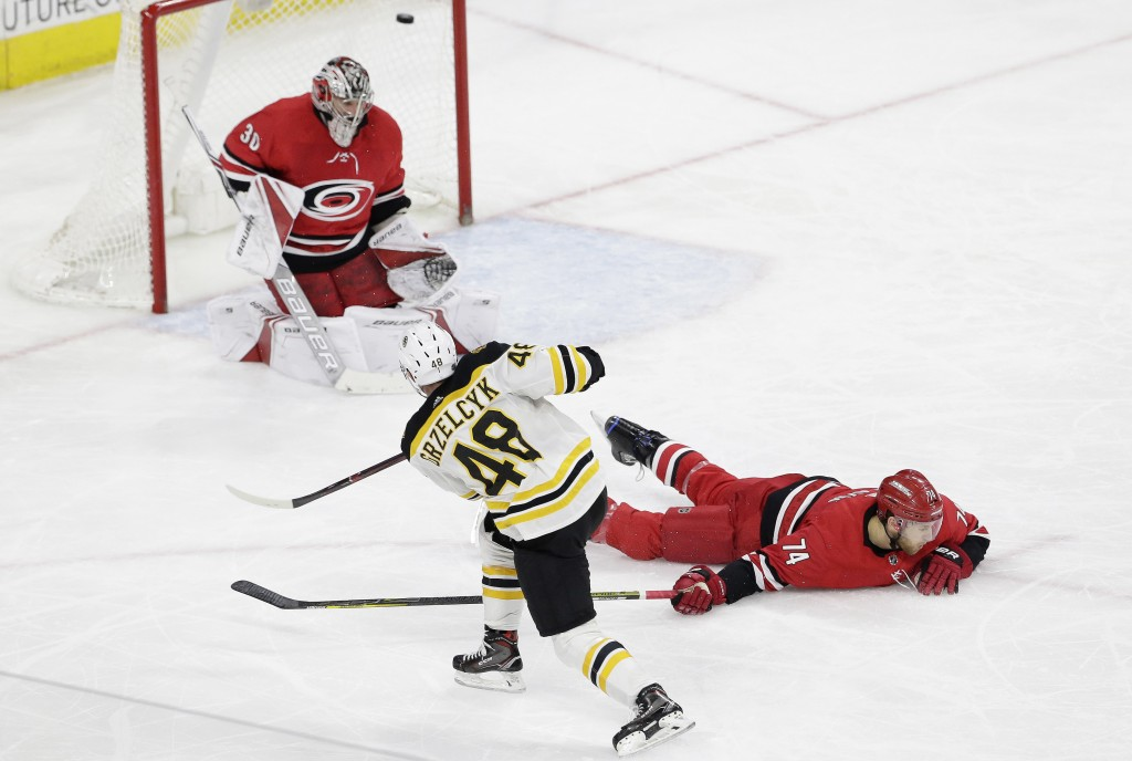 Boston Bruins' Matt Grzelcyk (48) scores against Carolina Hurricanes goalie Cam Ward (30) as Hurricanes' Jaccob Slavin (74) dives to block during the