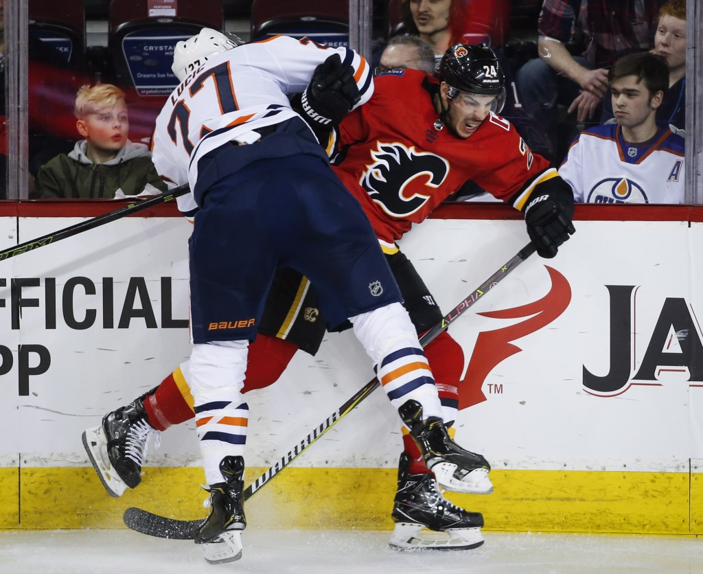 Edmonton Oilers left wing Milan Lucic (27) checks Calgary Flames defenseman Travis Hamonic (24) during the first period of an NHL hockey game in Calga