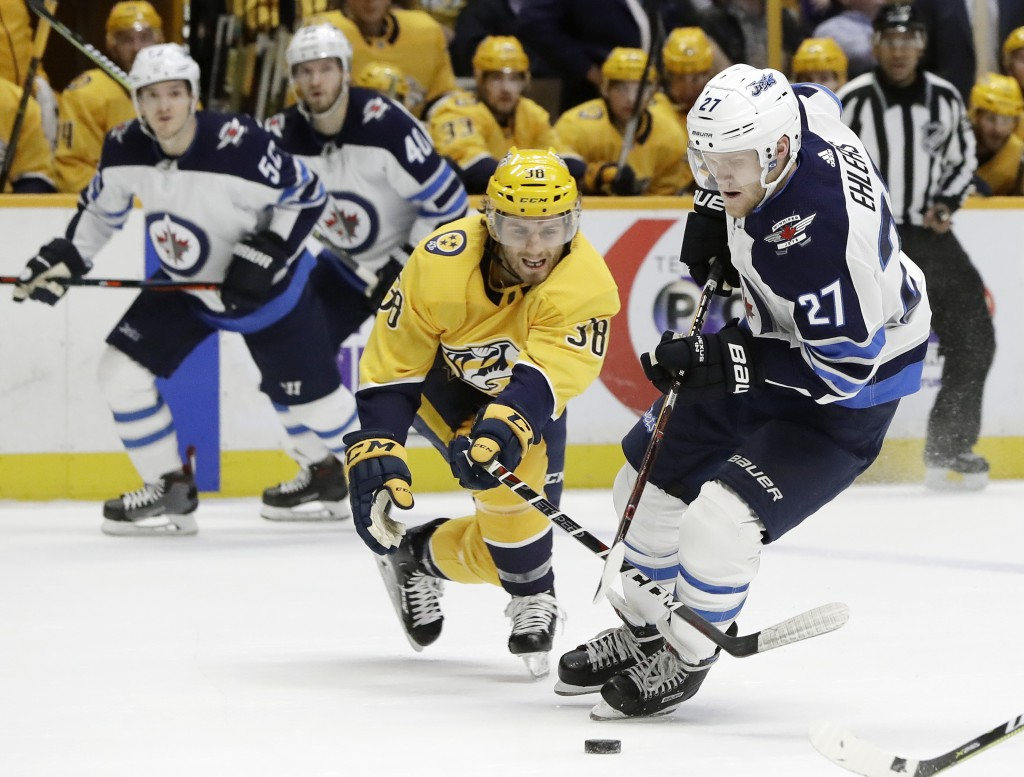Winnipeg Jets left wing Nikolaj Ehlers (27), of Denmark, moves the puck against Nashville Predators right wing Ryan Hartman (38) in the first period o