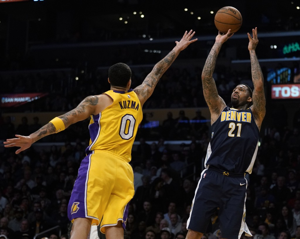Denver Nuggets forward Wilson Chandler, right, attempts a shot while Los Angeles Lakers forward Kyle Kuzma defends during the first half of an NBA bas