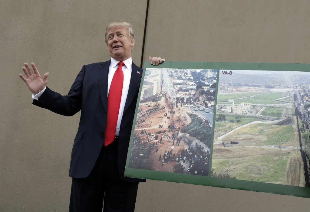 President Donald Trump holds a photo of the border area as he reviews border wall prototypes, Tuesday, March 13, 2018, in San Diego. (AP Photo/Evan Vu