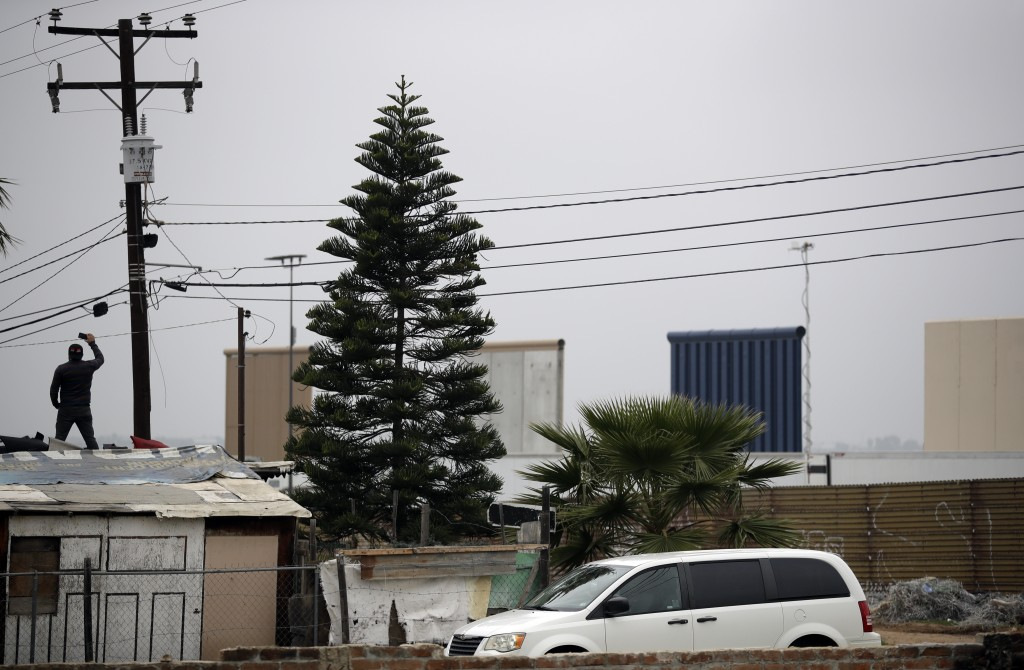 A man records with his phone as he stands on the roof of a home looking out to the border wall prototypes on the U.S. side in San Diego Tuesday, March