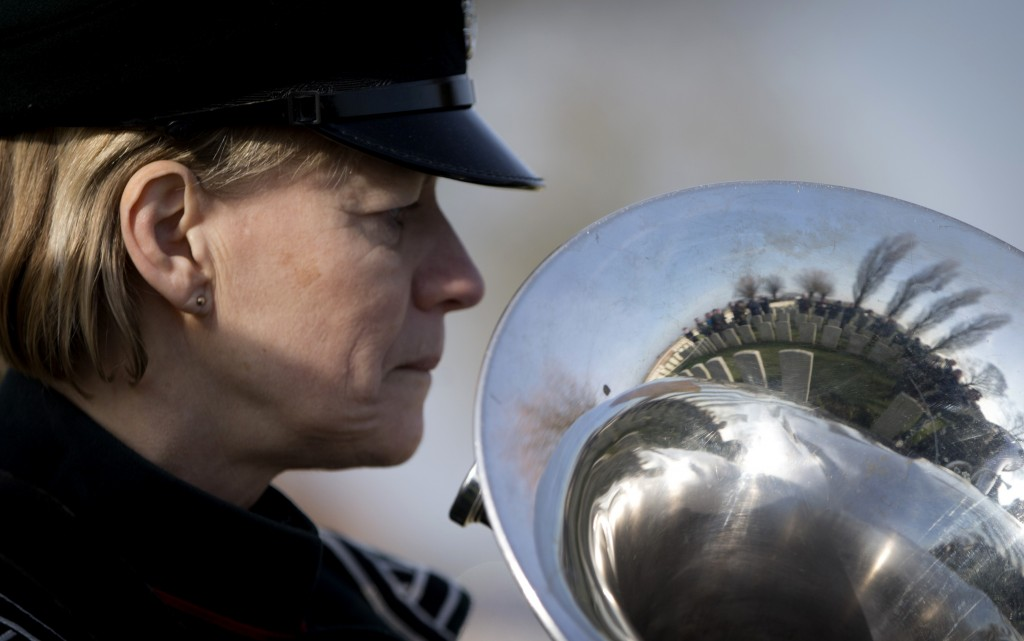 The CWGC Perth Cemetery is reflected in the horn of a musician during a reburial service for British Private Thomas Edmundson in Ypres, Belgium, Wedne