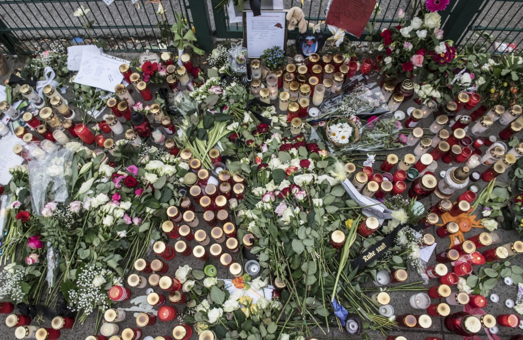 In this Monday, March 12, 2018 photo candles are laid down at the entrance of a sports hall in Berlin, Germany to honor the 14 years old Berlin studen
