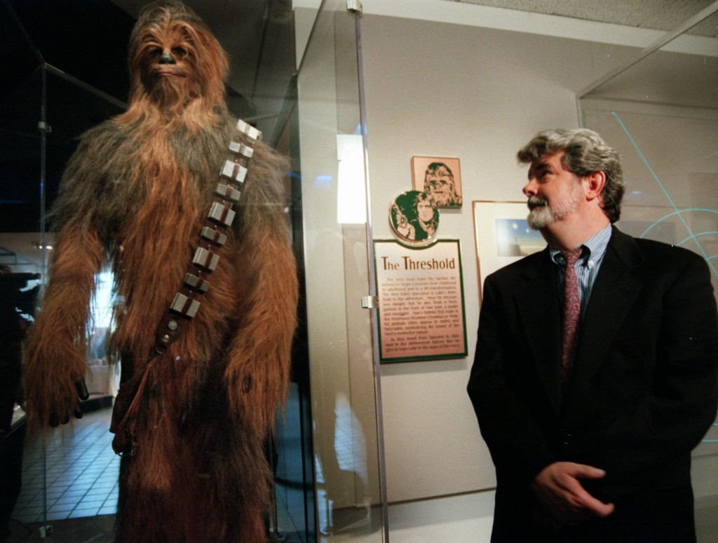"""FILE - In this Oct. 29, 1997 file photo, filmmaker George Lucas looks over a Chewbacca costume at the """"Star Wars"""" exhibit at the Smithsonian Instituti"""