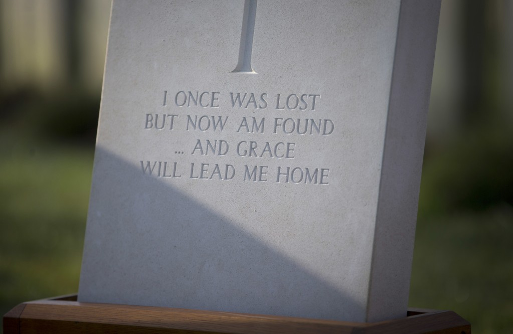 A newly engraved epitaph on the gravestone of British Private Thomas Edmundson during a re-burial service at CWGC Perth Cemetery in Ypres, Belgium, We