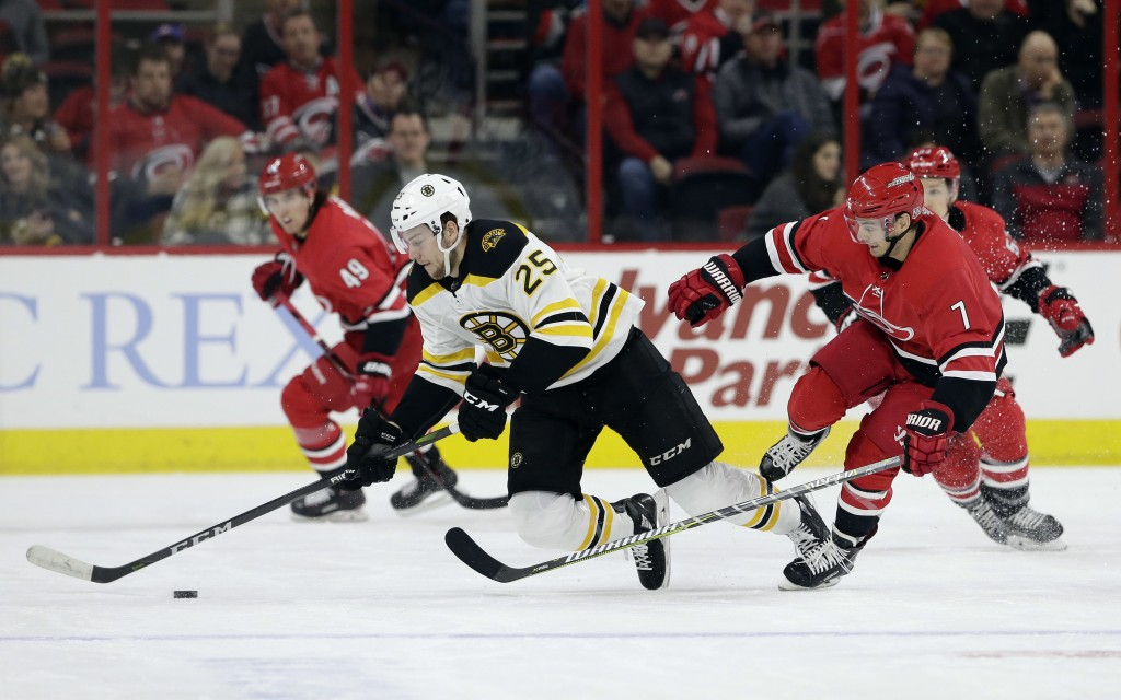 Boston Bruins' Brandon Carlo (25) chases the puck with Carolina Hurricanes' Derek Ryan (7) during the first period of an NHL hockey game in Raleigh, N
