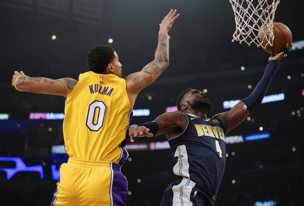 Denver Nuggets forward Paul Millsap, right, attempts a shot while Los Angeles Lakers forward Kyle Kuzma defends during the first half of an NBA basket