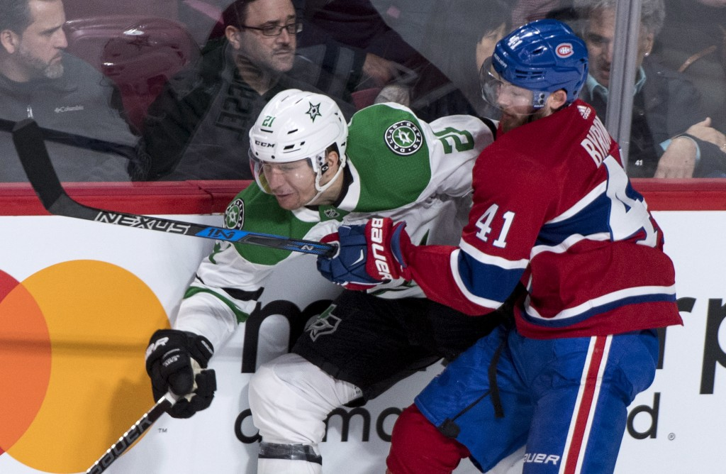 Dallas Stars left wing Antoine Roussel (21) is stopped by Montreal Canadiens left wing Paul Byron (41) during the first period of an NHL hockey game,