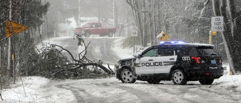 Sandwich Police block Route 6A at the Quaker Meetinghouse intersection where a tree downed live wires during a snowstorm, Tuesday, March 13, 2018 in S
