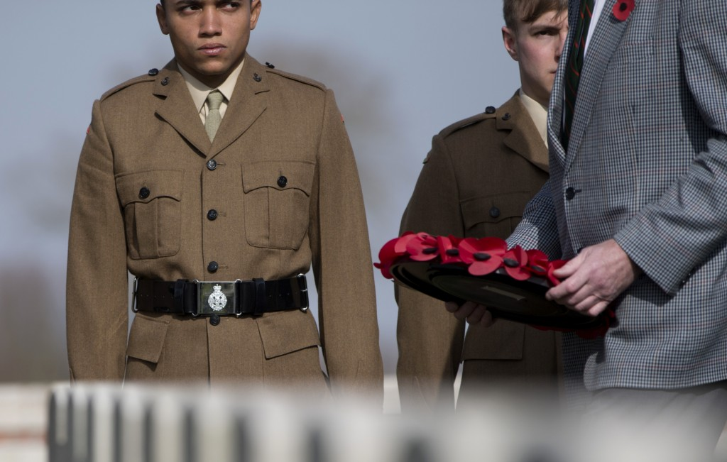 Soldiers watch as a man prepares to lay a poppy wreath for British Private Thomas Edmundson during a re-burial service at CWGC Perth Cemetery in Ypres