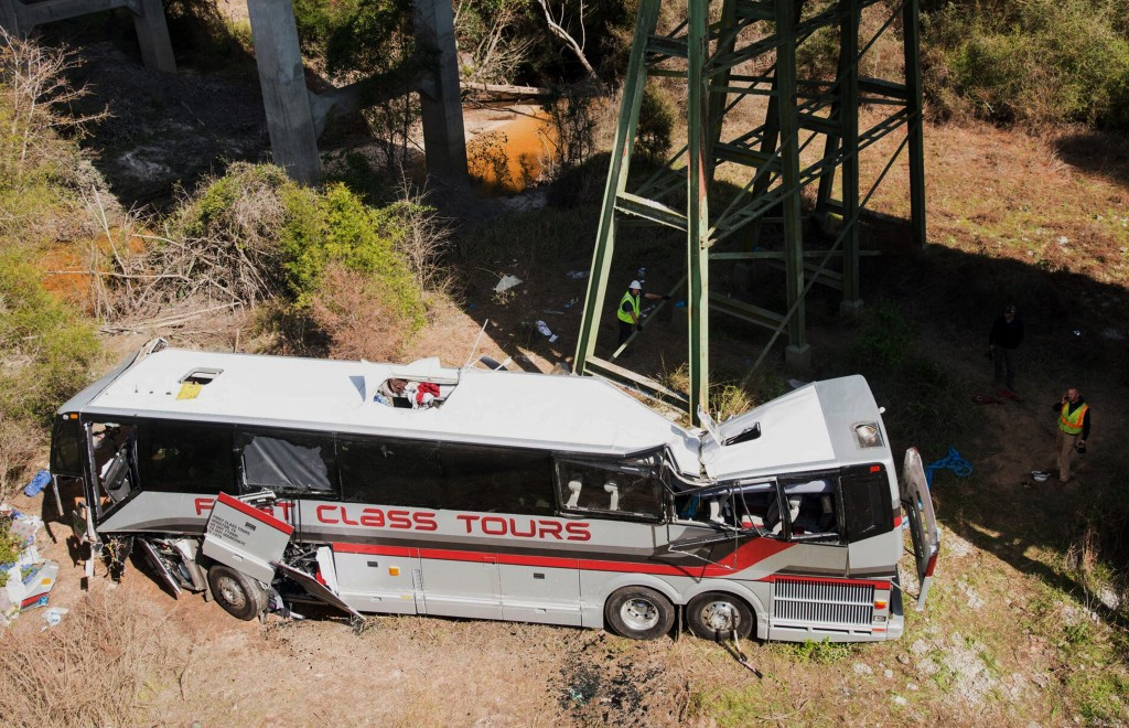 Emergency personnel walk around a bus that crashed into a ravine in Loxley, Ala., Tuesday, March 13, 2018. The bus carrying dozens of students and six