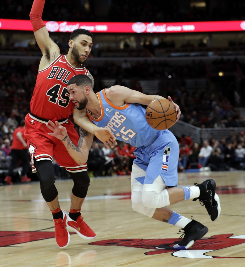 Los Angeles Clippers guard Austin Rivers, right, drives against Chicago Bulls guard Denzel Valentine during the first half of an NBA basketball game,