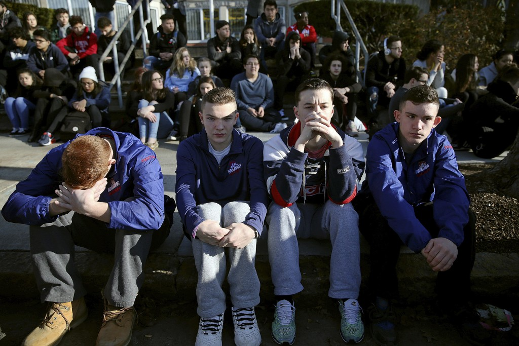 FILE - In this Feb. 28, 2018, file photo, Somerville High School students sit on the sidewalk on Highland Avenue during a student walkout at the schoo