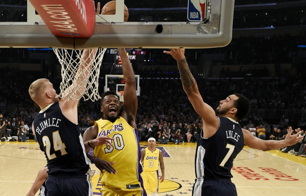 Los Angeles Lakers forward Julius Randle, center, attempts a shot while Denver Nuggets center Mason Plumlee, left, and forward Trey Lyles defend durin