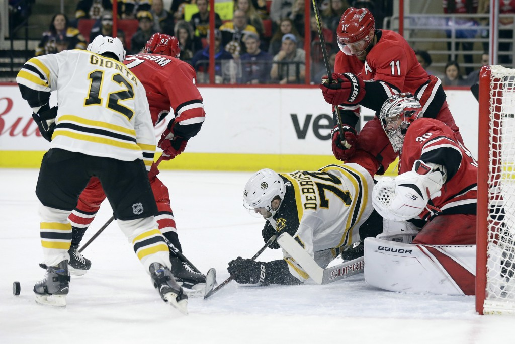 Boston Bruins' Jake DeBrusk (74) and Brian Gionta (12) try to take a shot against Carolina Hurricanes goalie Cam Ward (30) and Jordan Staal (11) durin