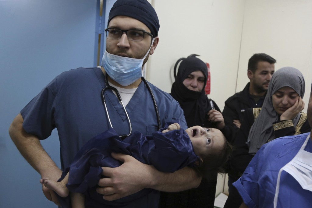 In this March 5, 2018 photo, the family of one-year-old Syrian refugee Eman Zatima watch as she is carried by a Jordanian doctor to the operating room