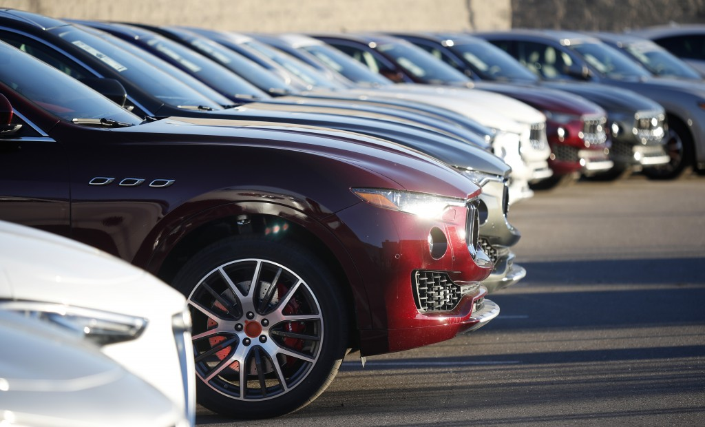 In this Sunday, Jan. 7, 2018, photograph, sun glints off the headlight housing of an unsold 2018 Maserati Levante in a long line of the high-end sport