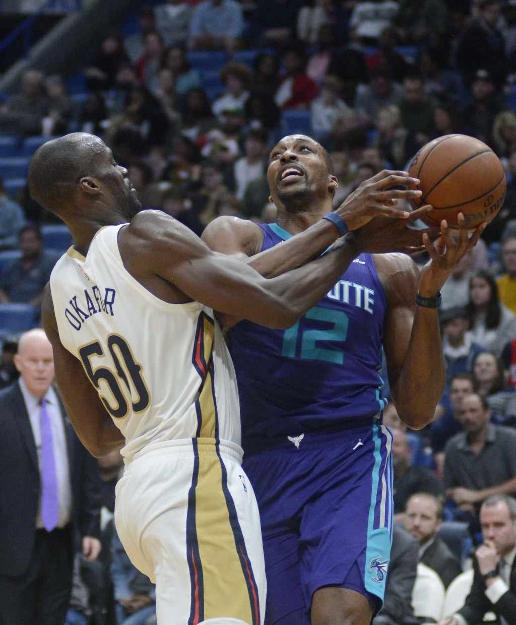 Charlotte Hornets' Dwight Howard (12) fights for the ball against New Orleans Pelicans center Emeka Okafor (50) in the first half of an NBA basketball