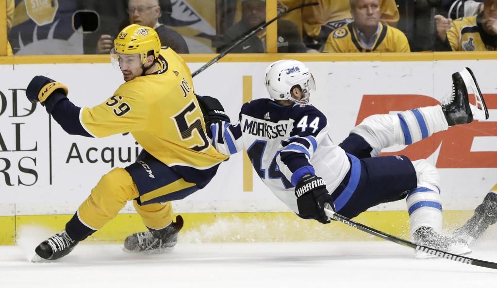 Winnipeg Jets defenseman Josh Morrissey (44) falls as Nashville Predators' Roman Josi (59), of Switzerland, skates past in the first period of an NHL