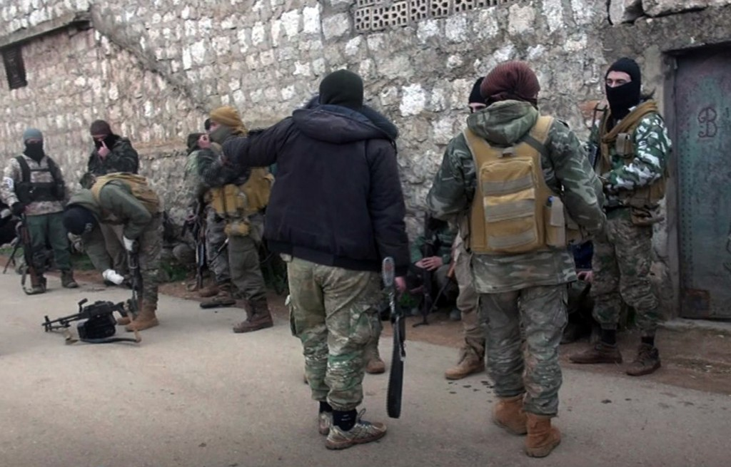 This photo released March 1, 2018, by the al-Qaida-affiliated Ibaa News Agency, purports to show al-Qaida-linked fighters from the al-Qaida-linked coa