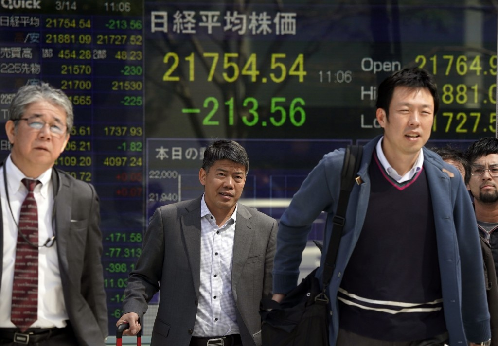 People walk in front of an electronic stock indicator of a securities firm in Tokyo, Wednesday, March 14, 2018. Asian shares fell Wednesday, taking th