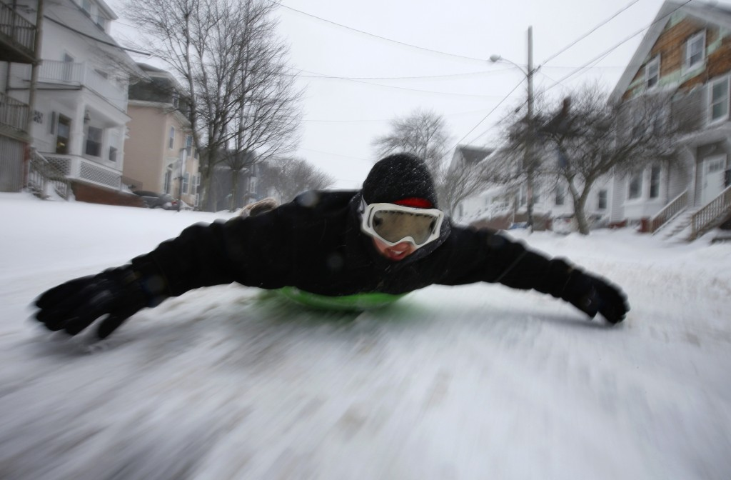 Gabby DiGiacomo, of Whitefield, Maine, slides down Congress Street in Portland, Maine, on a saucer during the latest winter storm, Tuesday, March 13,