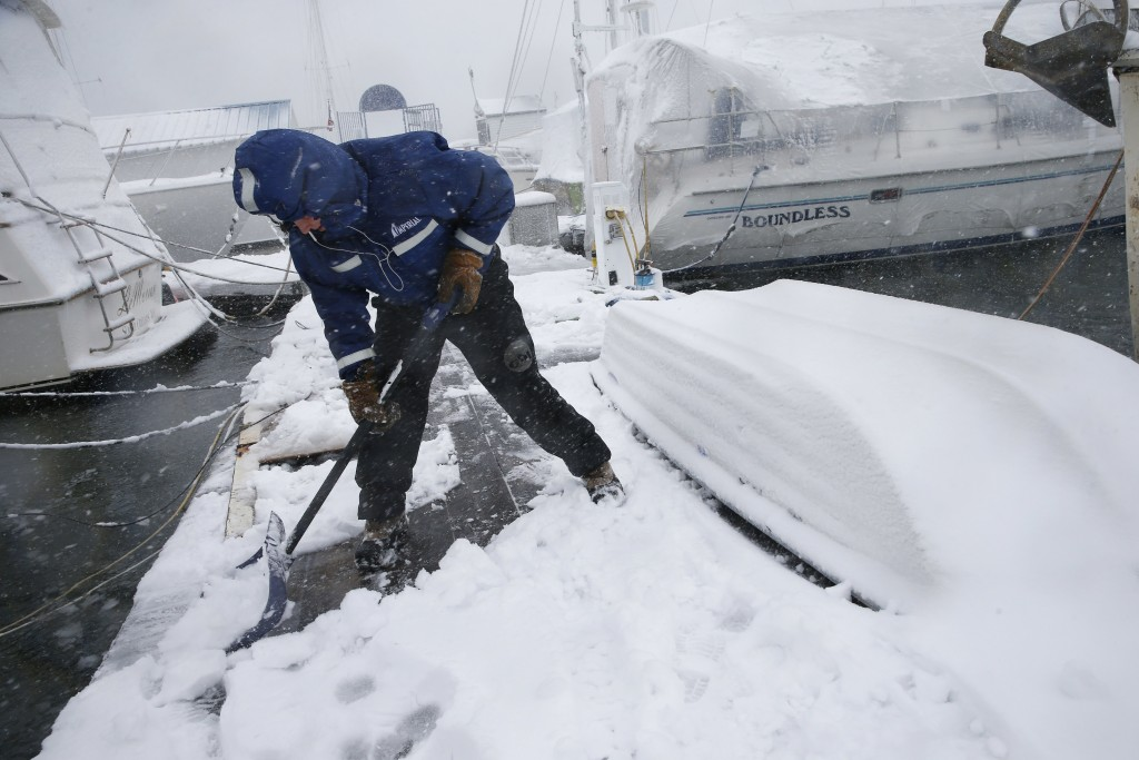 Gray Harrington clears snow from a dock at the Boston Harbor Shipyard and Marina in Boston, Tuesday, March 13, 2018. Boston finds itself in the bullse