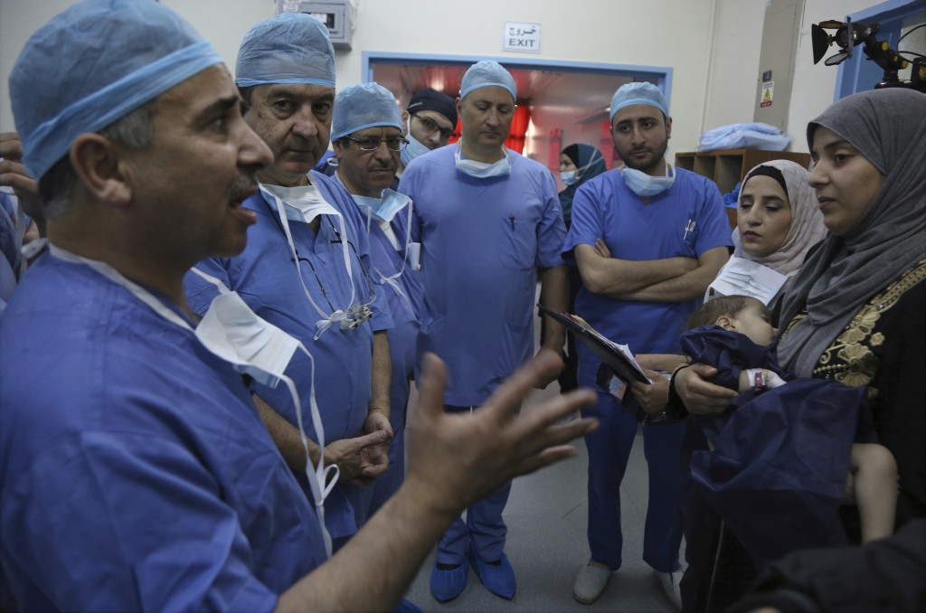 In this Monday, March 5, 2018 photo, Jordanian and Italian doctors brief Syrian refugee Sara al-Matoura before performing surgery on her one-year-old