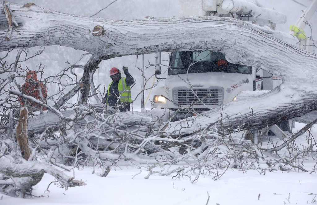 Workers remove a fallen tree from a road and repair power lines during a winter storm, Tuesday, March 13, 2018, in Norwell, Mass. A nor'easter that co