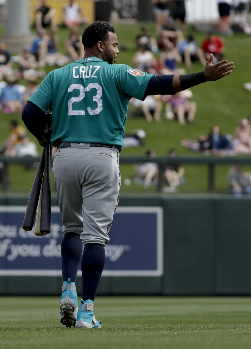 Seattle Mariners designated hitter Nelson Cruz gestures as he leaves during the first inning of a spring training baseball game against the Colorado R