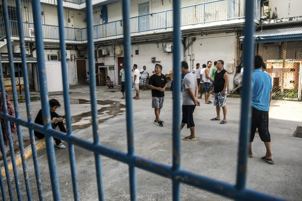 In this July 26, 2017 photo, Chinese laborers at the Imperial Pacific Casino gather in front of their living quarters before a protest in Saipan, the
